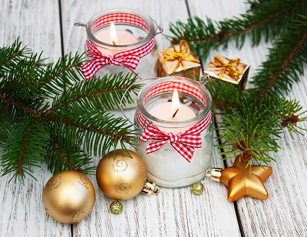 christmas decorations candles in glass jars with fir on a old wooden table